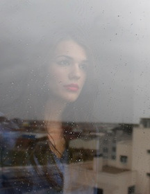 Woman looking out of window contemplating