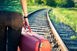 person-with-suitcase-waits-for-train-e1477411223771-300x199