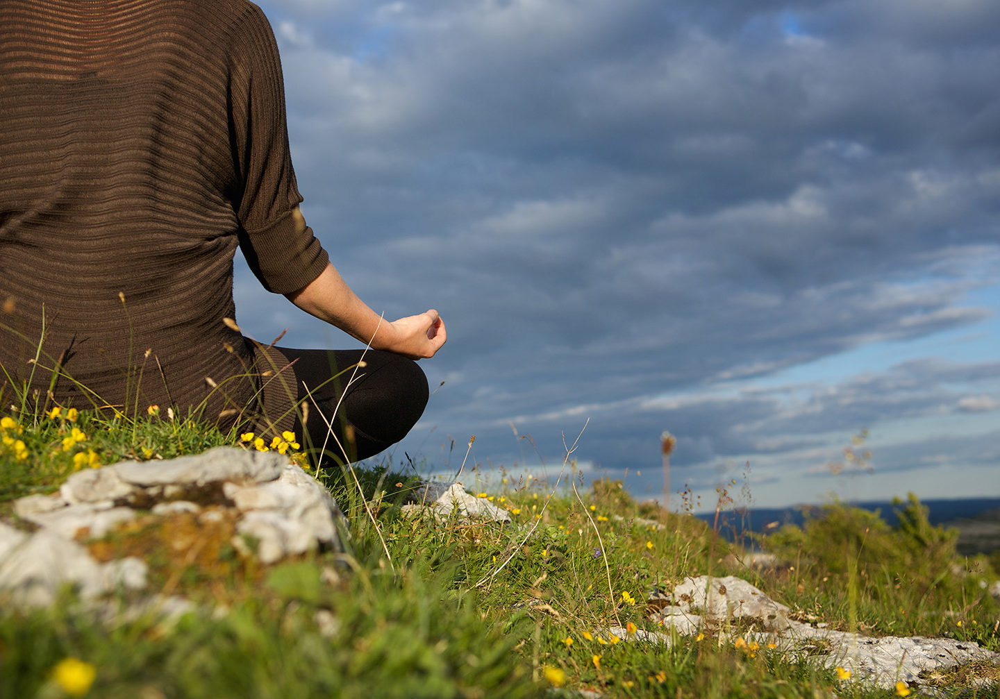 Young woman meditating in yoga position outdoors